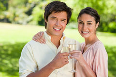 Two friends smiling while touching glasses of champagne royalty free stock photo