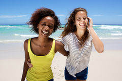 Two friends smiling and walking at the seaside Stock Photo