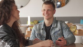 Two friends spend time at the cafe. Two caucasian friends spending time together at the cafe. Attractive blond man holding cellphone in his hand. Pretty curly stock video