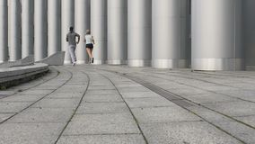 Two friends in sportswear sprint together next to huge pillars, urban workout. Stock footage stock video