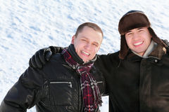 Two friends stand on snow in embrace and smile. Winter Royalty Free Stock Photos
