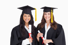 Two friends stand together after graduating Royalty Free Stock Photos