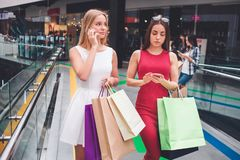 Two friends are standing together with many bags. They are on shopping. Blonde girl is talking on the phone while. Brunette is looking at her gadget royalty free stock photo