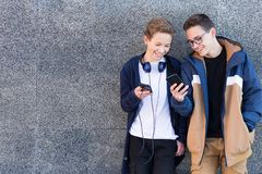 Two friends standing together near the wall outdoors looking at mobile phone. Copy space stock images