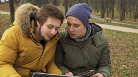 Two friends students uses laptop and tablet outdoors. Two students sits in the park and discuss something looking on laptop and tablet. Friends talks with each stock video footage