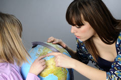 Two friends studying on globe Stock Photo