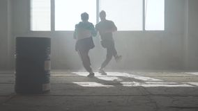 Training skilled hip hopers. Two friends of successful dancers are dancing breakdance in an abandoned dusty building stock video