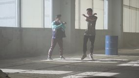 Two friends of successful dancers are dancing breakdance in an abandoned dusty building. Contemporary. Hip hop culture stock video