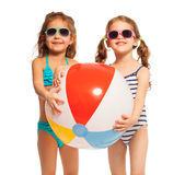Two friends in sunglasses holding big wind-ball. Two smiling friends in sunglasses and swimwear holding together big colored wind-ball Royalty Free Stock Photo