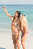 Two friends in swimsuits taking a selfie Stock Photos