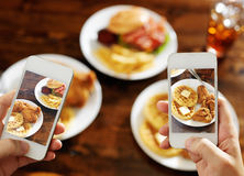 Two friends taking photo of their food with smartphones. Consisting of chicken and waffles and burgers Royalty Free Stock Image