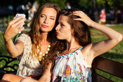 Two friends taking selfie by smartphone Stock Photos