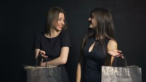 Two Friends Talk about Shopping. Two smiling caucasian girlfriends with black shopping bags talking about shopping on black friday, isolated indoor shot stock video footage