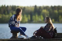 Two friends teen girls spend time together at the pier of the river. Nature. Stock Images