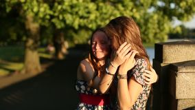Two  friends teenage girls foolishly fun talking on the city promenade at sunset time. stock video
