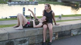 Two  friends teenage girls sitting and close talking on the city promenade. stock video footage