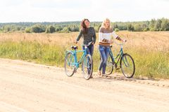 Two friends at their bike walking outdoors Royalty Free Stock Images