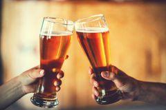 Two friends toasting with glasses of light beer at the pub. Beautiful background of the Oktoberfest. fine grain. Soft focus. Shallow DOF Royalty Free Stock Image