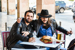 Two friends/tourists are eating outside in the open. Royalty Free Stock Images