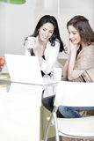 Two friends using a laptop Stock Photography