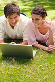 Two friends using a laptop together. While lying down in the park Royalty Free Stock Image