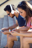 Two friends using mobile phone and listening to music in the str Royalty Free Stock Image