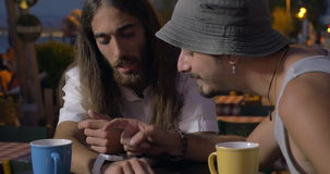 Two friends using smartwatch in street cafe. Two men using smart watch while sitting in street cafe on waterfront in late evening stock footage