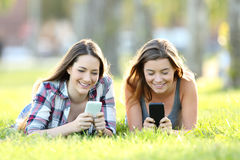 Two friends using their smart phones on the grass. Front view of two happy friends using their smart phones on the grass in a park Stock Images