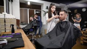 Two friends visiting modern barbershop. Handsome hipsters sitting against mirror and working with hairstylists. Smiling stock footage