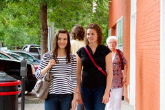 Two friends walking. With others on street royalty free stock image