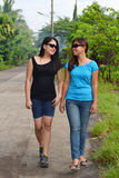 Two friends walking. Two Asian female friends having fun with conversation while walking in the street royalty free stock photos