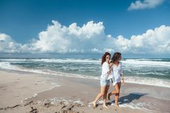 Two friends walking on the beach royalty free stock photo