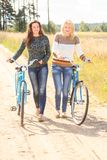 Two friends walking with bicycles Royalty Free Stock Photo