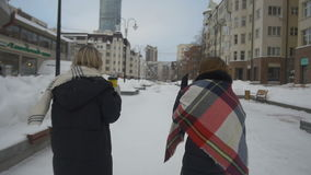 Two friends walking down the street and drink coffee in winter.  stock video footage