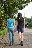 Two friends walking. Two female friends walking in the street of a country side royalty free stock image