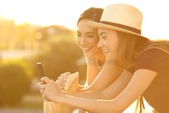 Two friends watching on line content at sunset. Two joyful friends watching on line content in a smart phone in a balcony at sunset Stock Photos