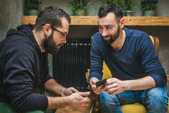 Two friends watching media content in a smart phone stock photo
