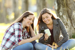 Two friends watching media in their smart phones. Two happy friends watching media content in their smart phones sitting on the grass in a park Stock Image