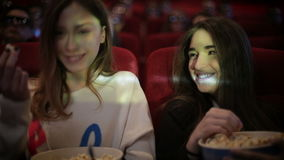 Two friends watching movie in cinema stock footage