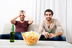 Two Friends watching passionately TV with Beer and Chips Stock Photos