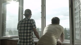 Two friends watching the sunset from the window. HD stock footage