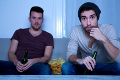 Two friends watching television at home Stock Image