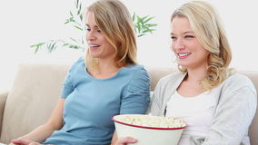 Two friends watching TV. With popcorn stock video footage