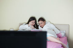 Two friends wearing bathrobes watching a scary movie on bed Stock Photography