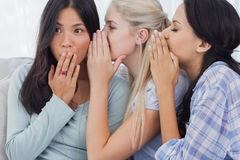 Two friends whispering secrets to shocked brunette. At home on couch royalty free stock photography