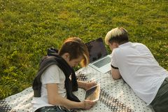 Two friends in white t-shirts sitting on grass in park and watching tablet and laptop. Have fun on line royalty free stock photo