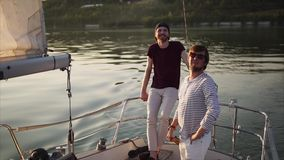 Two friends who are engaged in sailing enjoy the sunset in the evening. Young friends rest on the yacht in the evening, friends are engaged in sailing in the stock video