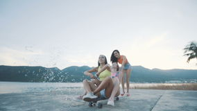 Two friends woman sits on longboard, which is run by smiling girl on the beach. stock footage