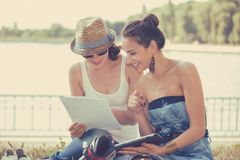 Two friends women outdoors studying and looking happy Stock Photo