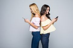 Two beauty friends women standing back to back and typing message on phones. Two friends women standing back to back and typing message on phones royalty free stock image